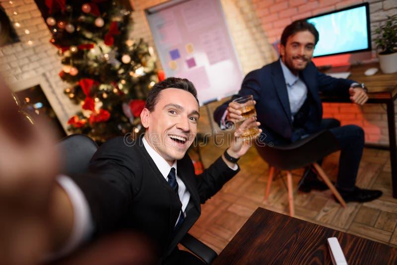 Zakenmanzitting in bureau en het werken aan Nieuwjaar` s Vooravond Hij maakt een selfie met zijn ring, die naast hem zit royalty-vrije stock foto
