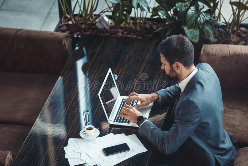 Zakenmanzitting in commercieel centrumrestaurant het typen op laptop hoogste mening royalty-vrije stock foto's