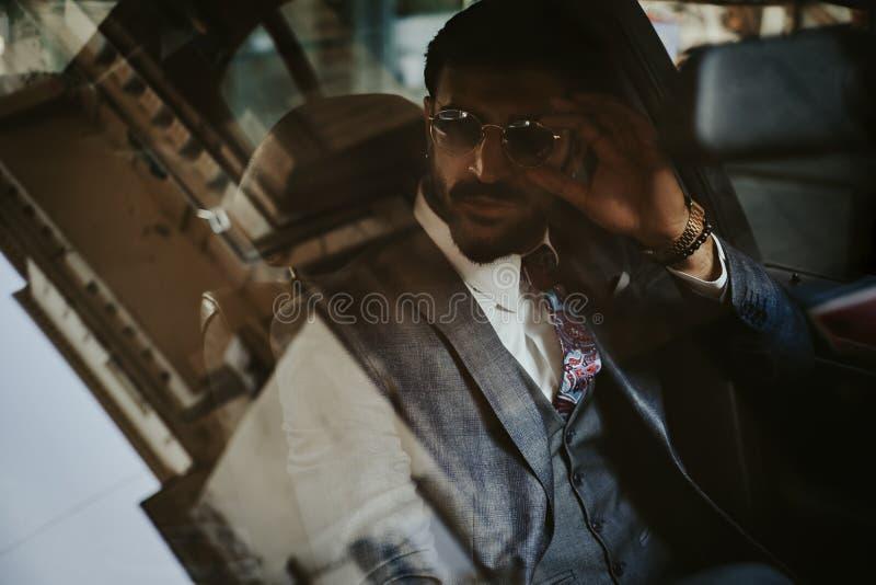 Zakenmanzitting in de auto en holding zijn zonnebril royalty-vrije stock afbeeldingen