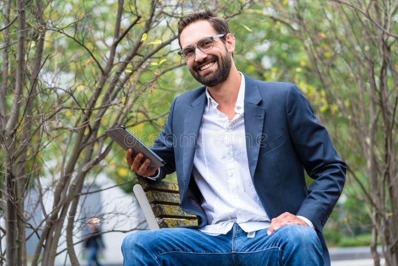 Zakenmanzitting die op bank digitale tablet houden royalty-vrije stock fotografie