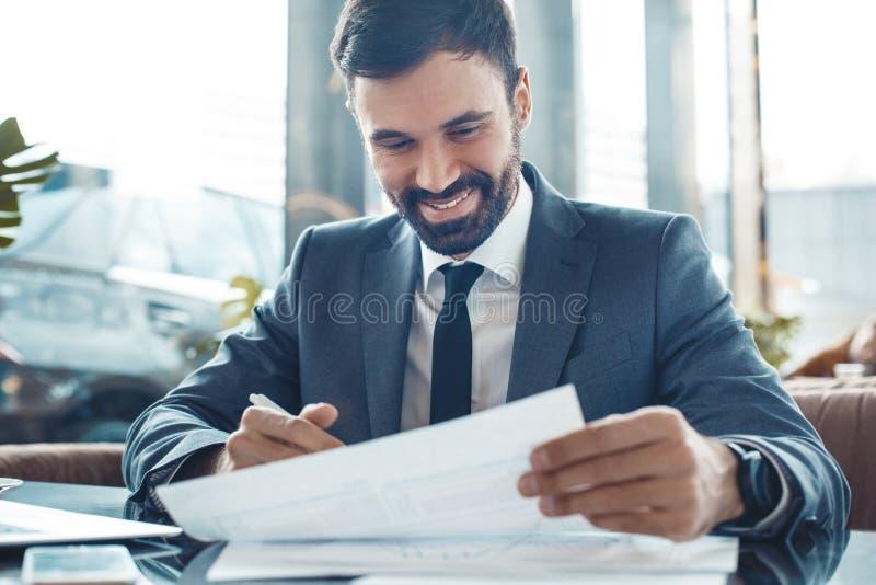 Zakenmanzitting in een commercieel centrumrestaurant die gelukkige documenten ondertekenen royalty-vrije stock fotografie