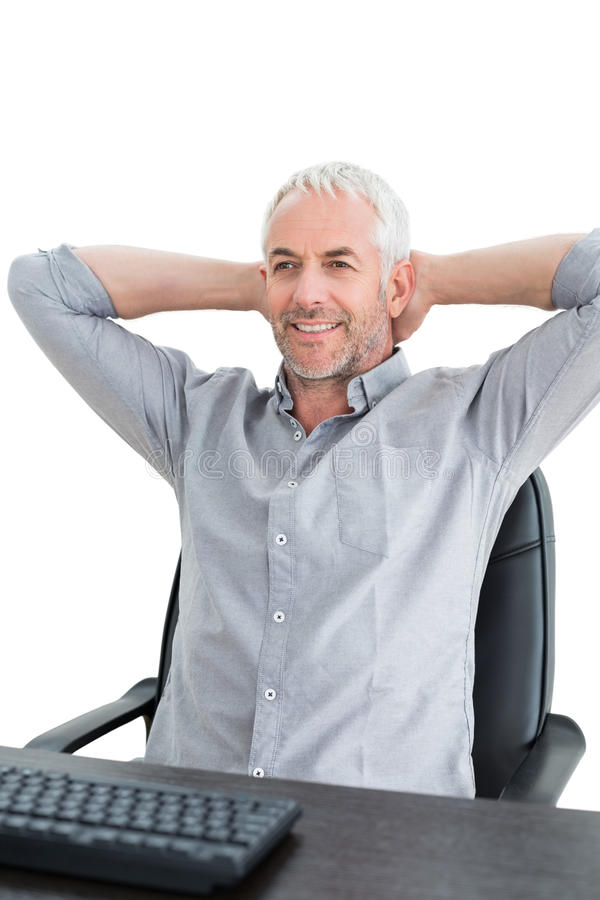 Zakenmanzitting met handen achter hoofd bij bureau royalty-vrije stock afbeelding