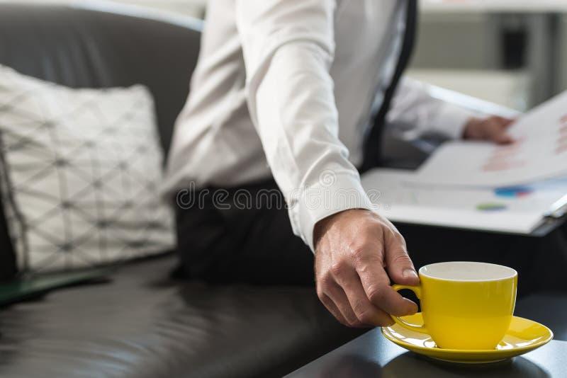 Zakenmanzitting op een bureaulaag met administratie stock afbeelding