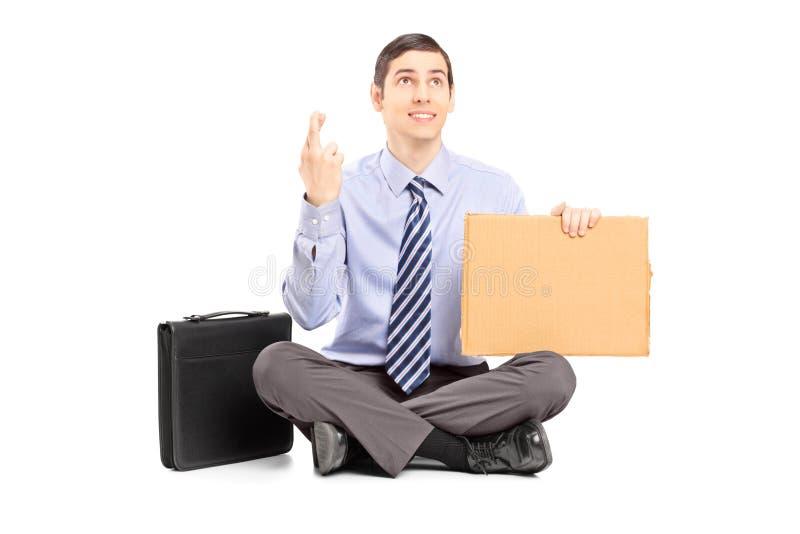 Zakenmanzitting op grond met gekruiste vingers en holding a stock afbeelding