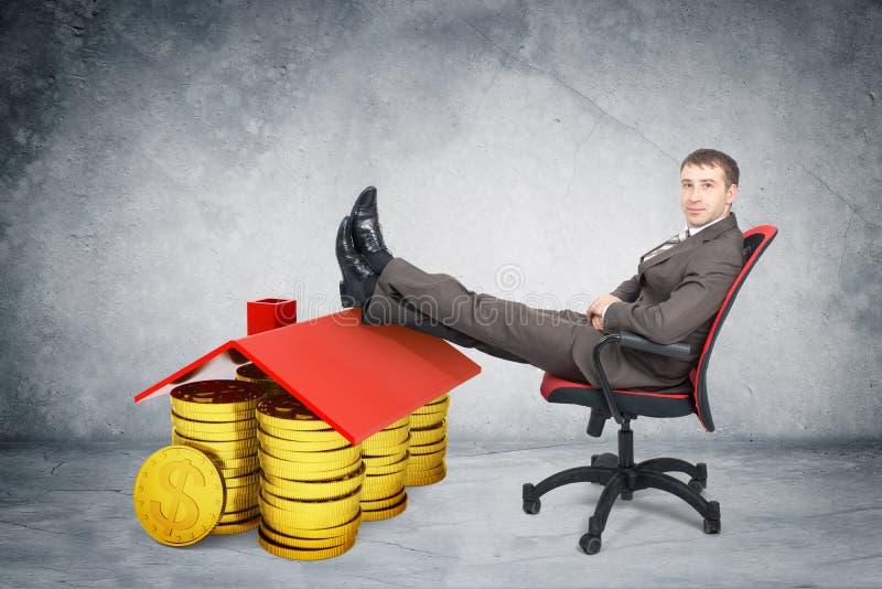 Zakenmanzitting op stoel met muntstukken en dak stock fotografie