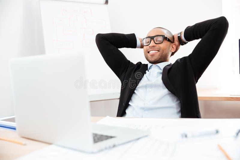 Zakenmanzitting terug in zijn stoel het ontspannen stock foto