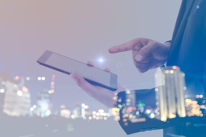 Zakenrelatieconcept Dubbele blootstelling die van zakenman digitale tablet en cityscape abstracte bokehachtergrond houden royalty-vrije stock afbeeldingen