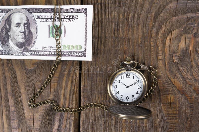 Zakhorloge verbonden aan contant geld in de boom De tijd is geld royalty-vrije stock afbeelding