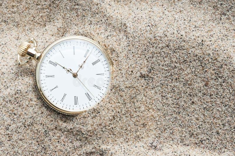 Zakhorloge in zand wordt begraven dat stock afbeeldingen