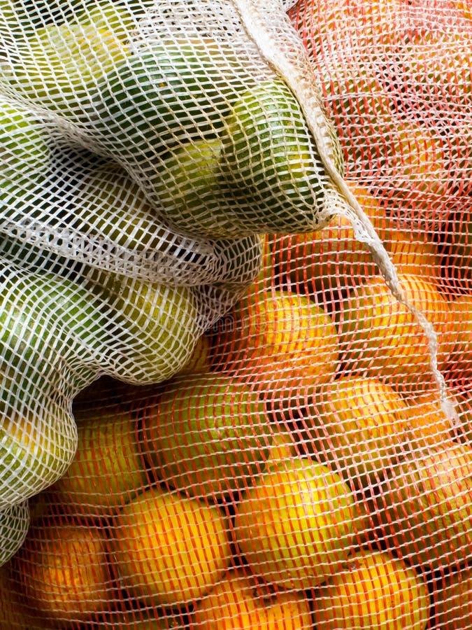 Zakken met sinaasappelen en citroenen worden gevuld die stock fotografie
