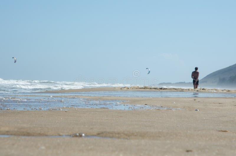 Zakończenie Morze plaża z nadchodzącą falą Na średnim planie jest mężczyzna fotografia stock