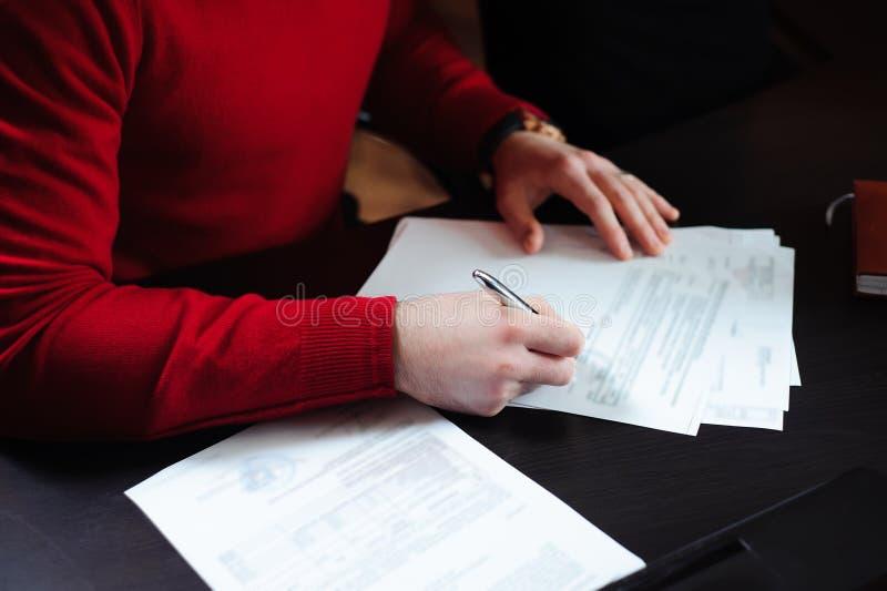 Zakończenie samiec ręki z piórem nad dokumentem obrazy stock