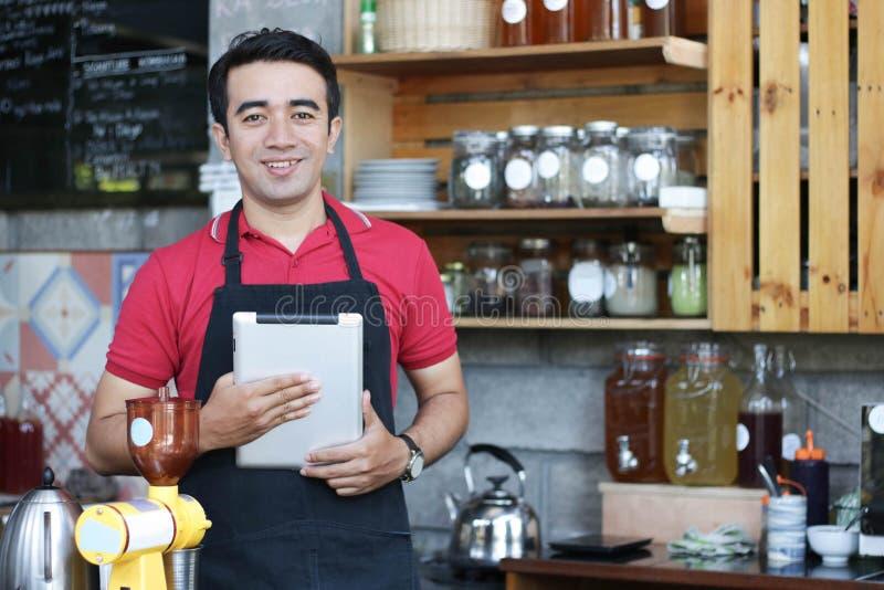 Zakończenie w górę azjatykciego mężczyzny barista mienia uśmiechniętego laptopu sprawdza rozkazy i zapas za kontuarem cukierniana obrazy royalty free