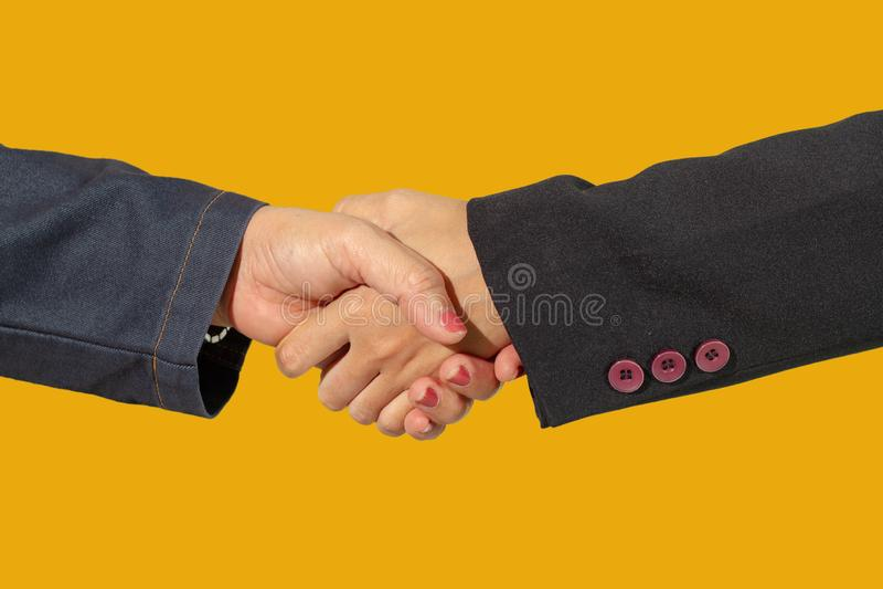 Zakończenie w górę biznesowego uścisku dłoni odizolowywa na żółtym blackground zdjęcia stock