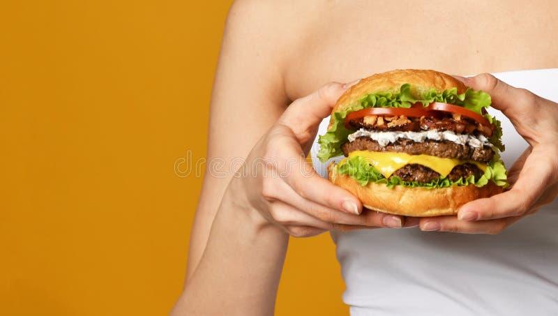 Zakończenie w górę fotografii duża cheeseburger hamburgeru kanapka z wołowina bekonowym serem pomidorami na kolorze żółtym i obrazy royalty free