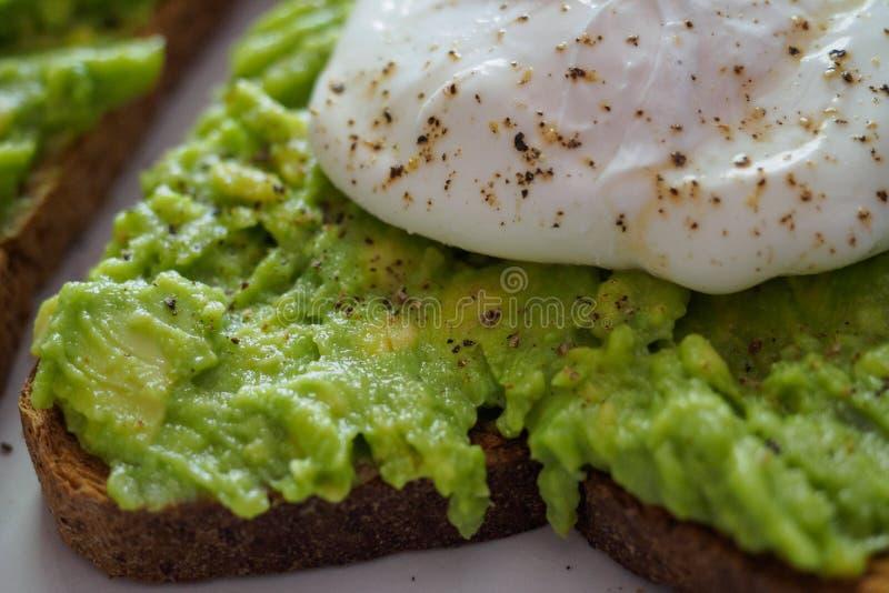 Zakończenie w górę kłusującego jajka na roztrzaskującej avocado grzance z zmielonym czarnym pieprzem zdjęcia stock