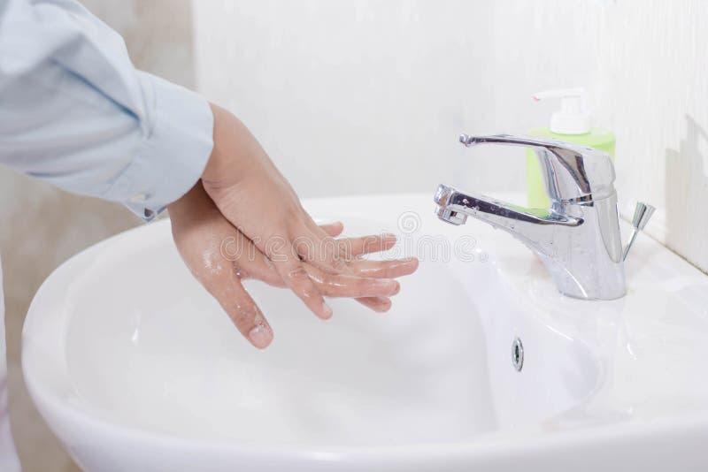 Zakończenie w górę kobiety lekarki myje jej backhand w białym zlew z lać się wodę, mydło i pianę, fotografia royalty free