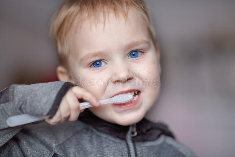 Zakończenie w górę portreta śliczna caucasian chłopiec z bardzo poważnym twarzy wyrażeniem czyści zęby z zębami szczotkuje, sam B zdjęcia royalty free