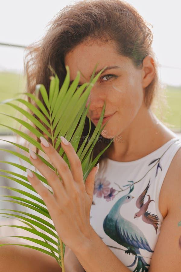 Zakończenie w górę portreta atrakcyjna powabna młoda kobieta jest ubranym pływanie kostiumu nakrycia twarz z palmowym liściem z k fotografia royalty free
