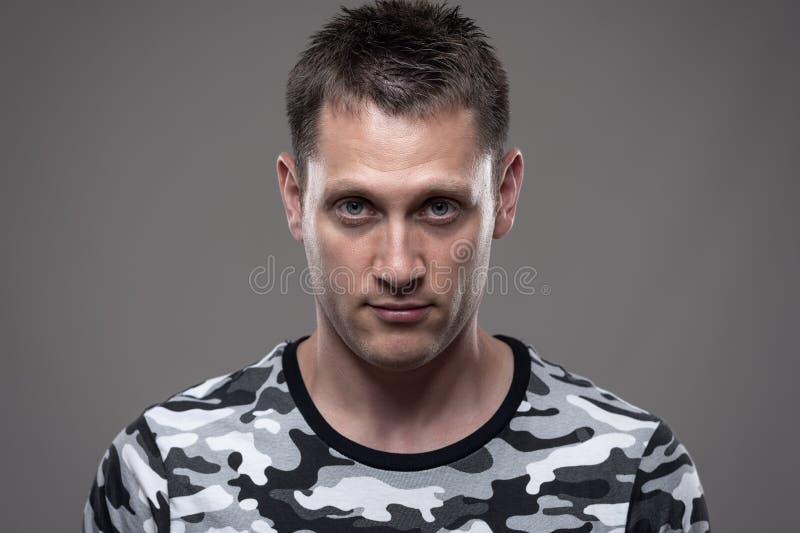 Zakończenie w górę portreta młody dorosły mężczyzna w wojska koszulowy patrzeć intensywny przy kamerą przy uwagą obrazy stock