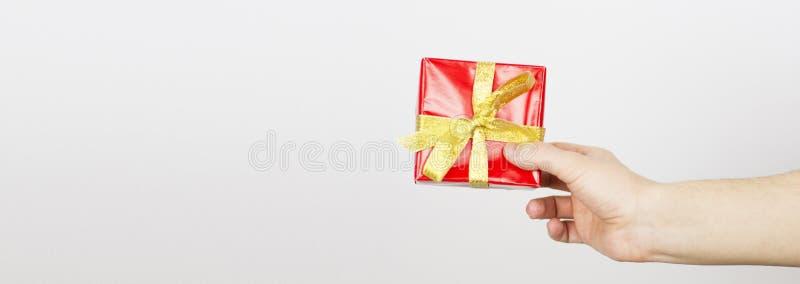 Zakończenie w górę strzału trzyma małego prezent zawijający z żółtym faborkiem żeńska ręka Mały prezent w rękach kobieta odizolow zdjęcia royalty free