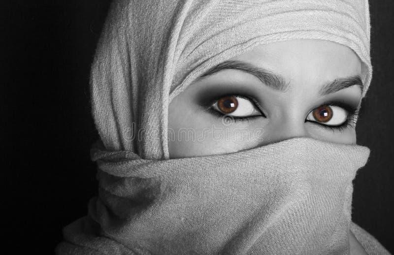 Zakończeń pięknych tajemniczych oczu wschodnia kobieta jest ubranym hijab czarny white zdjęcia stock