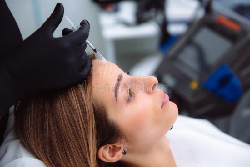 Zakończenia cosmetologist i twarzy ` s piękne żeńskie ręki z strzykawką podczas twarzowych piękno zastrzyków Odmładzanie i obraz royalty free