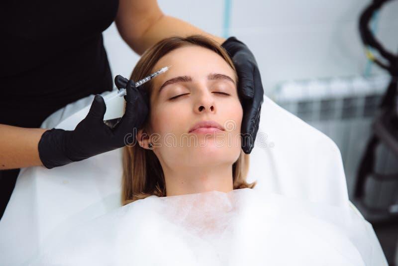 Zakończenia cosmetologist i twarzy ` s piękne żeńskie ręki z strzykawką podczas twarzowych piękno zastrzyków Odmładzanie i zdjęcia stock