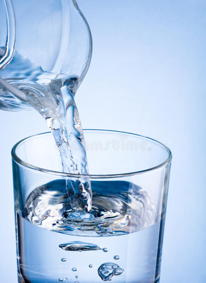 Zakończenia dolewania woda od dzbanka w szkło na błękitnym backgroun zdjęcia royalty free