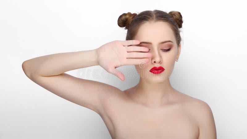 Zakończenia piękna portret młoda piękna kobieta z czystej świeżej zdrowej skóry babeczki śmiesznym uczesaniem howing jej palmy na obrazy stock