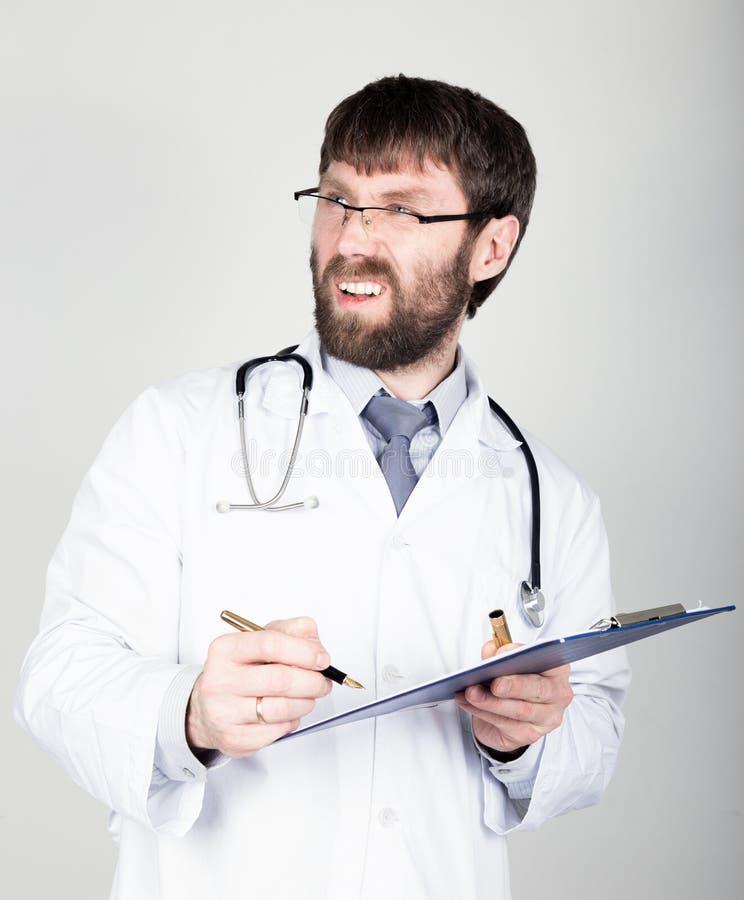 Zakończenia portret Doktorski mienie mapnik dla notatki, stetoskop wokoło jego szyi on discontentedly patrzeje obraz royalty free