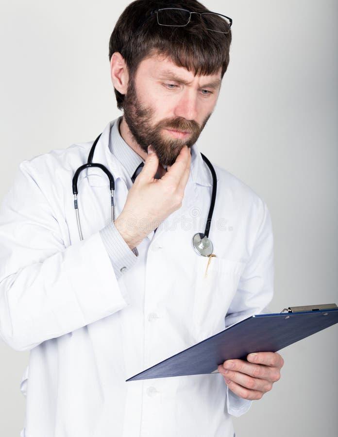 Zakończenia portret Doktorski mienie mapnik dla notatki, stetoskop wokoło jego szyi Naciera jego podbródek dyferencja obrazy stock