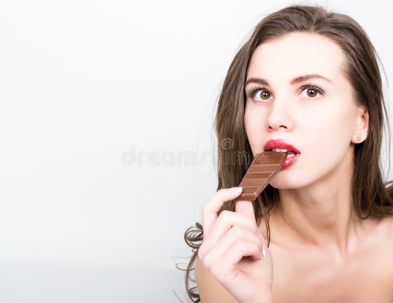 Zakończenia portret piękna seksowna kobieta je czekoladę z czerwonymi wargami fotografia royalty free