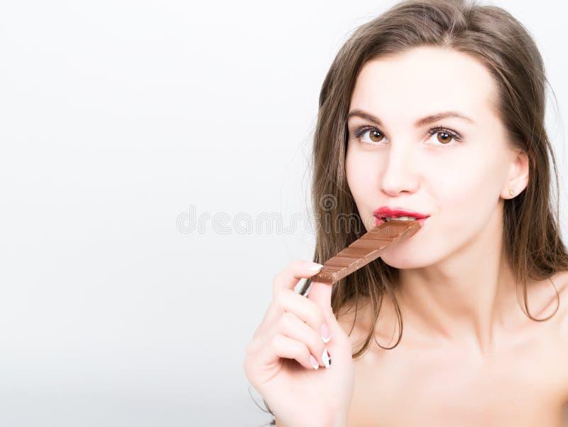Zakończenia portret piękna seksowna kobieta je czekoladę z czerwonymi wargami fotografia stock