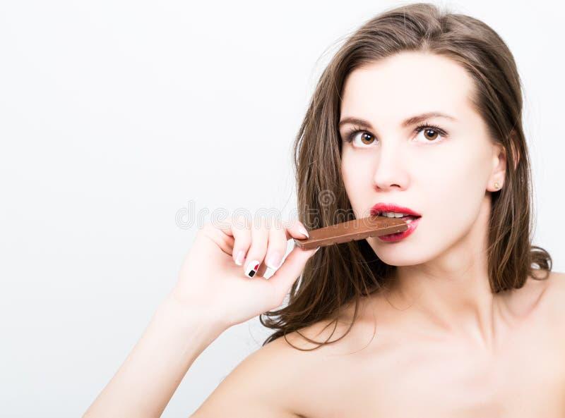 Zakończenia portret piękna seksowna kobieta je czekoladę z czerwonymi wargami obraz royalty free