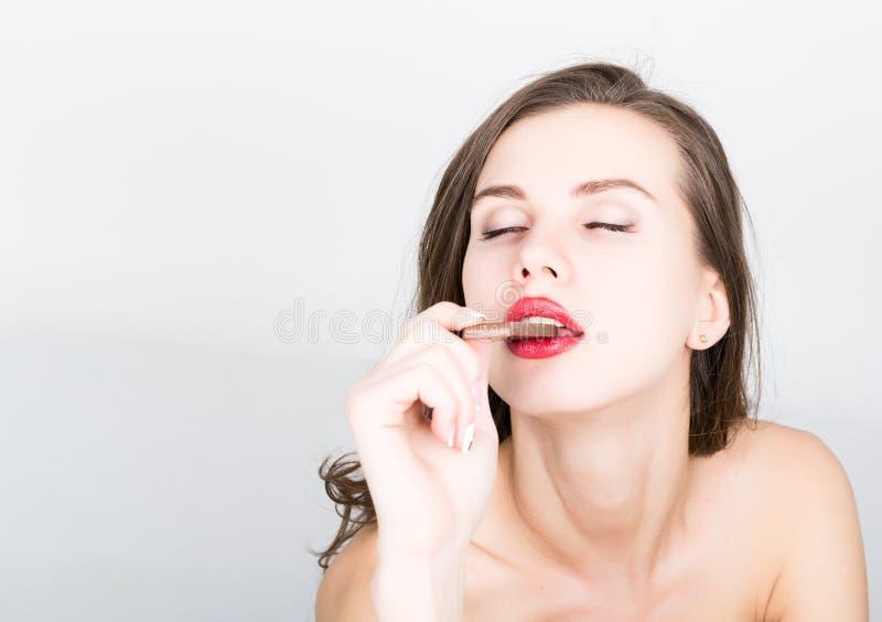 Zakończenia portret piękna seksowna kobieta je czekoladę z czerwonymi wargami zdjęcia royalty free