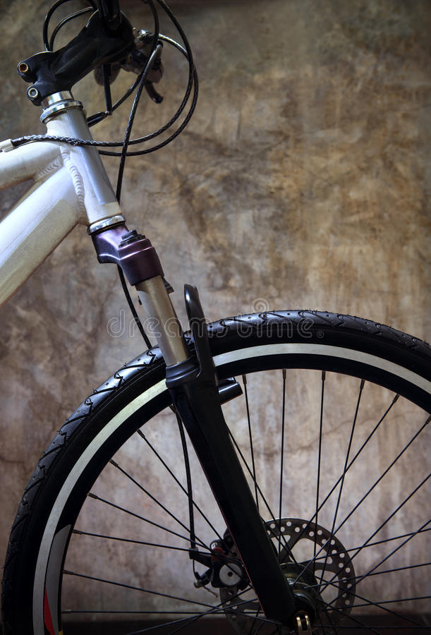 Zakończenia up - frontowego koła opona rower górski przeciw grungy cementowi obrazy stock
