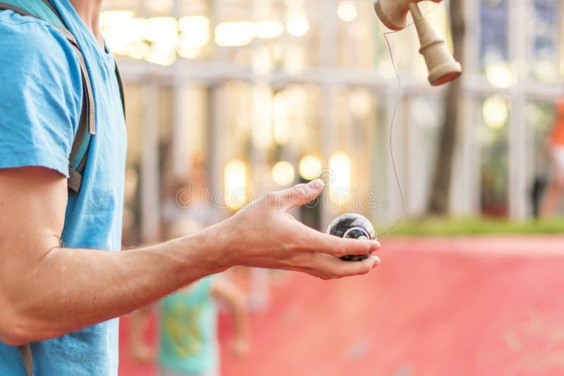 Zakończenia up ręki bawić się kendama japaneese zabawkę w ulicie zdjęcia stock