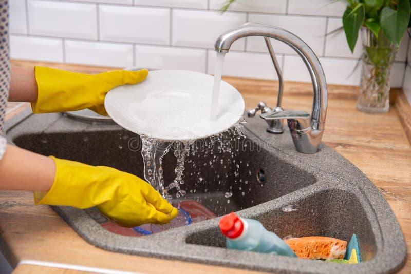 Zakończenia up ręki kobiety domycia naczynia w kuchni obrazy royalty free