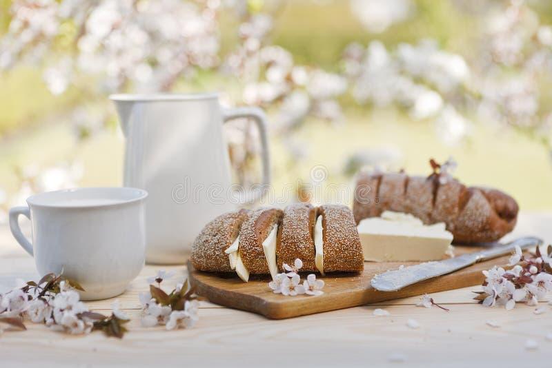 Zakończenie świeży domowej roboty chleb z masłem na drewnianej desce z zimna mlekiem w słoju i szklany plenerowym na zamazanym kw obraz stock