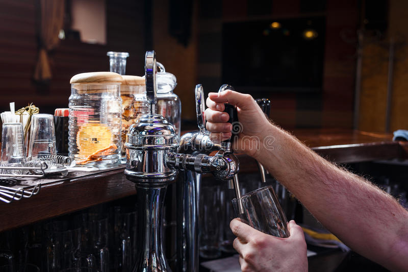 Zakończenie barman ręki nalewa piwo obrazy stock