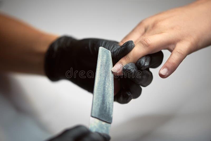 Zakończenie beautician ręki w czarnych rękawiczkach segreguje klient kobiety gwoździe w kształcie używać szmerglową deskę obrazy royalty free
