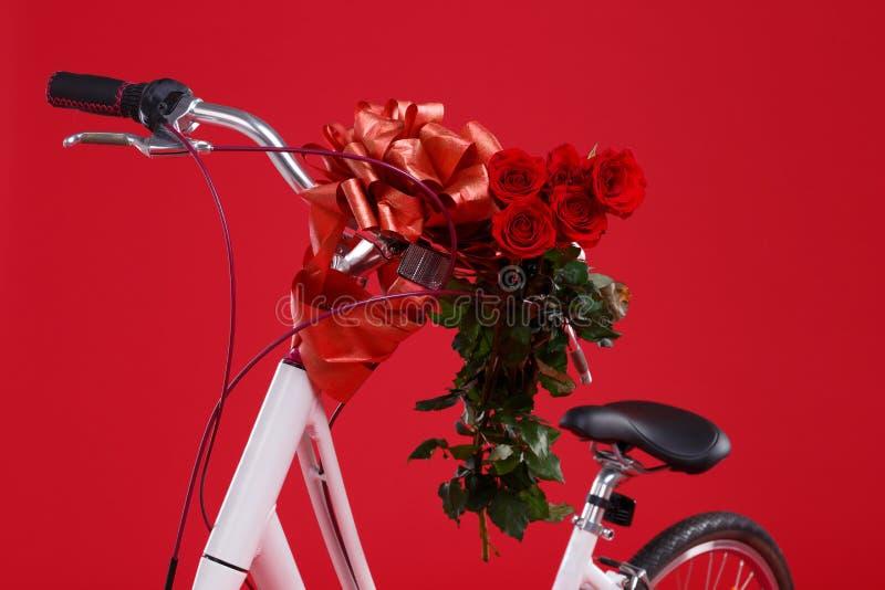 Zakończenie biały bicykl na czerwonym tle z wielkim prezenta łękiem i bukiet róże zdjęcie stock