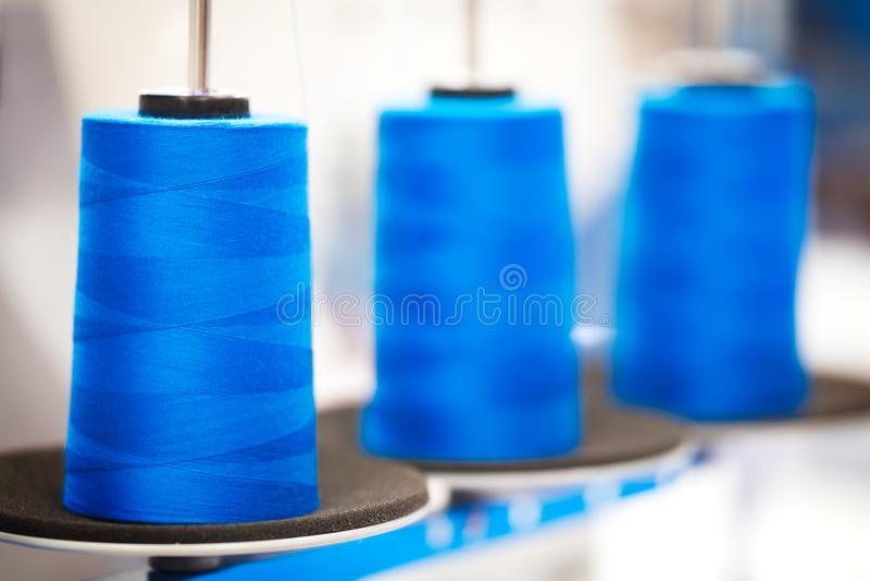 Zakończenie bobiny z błękitną barwioną nicią dla przemysłowych tekstylnych maszyn, błękitny textured sieć sztandaru tło zdjęcia stock