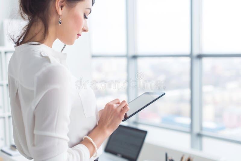 Zakończenie bocznego widoku portret pracownik texting, wysyła i czyta wiadomości podczas jej przerwy przy miejscem pracy, obrazy stock