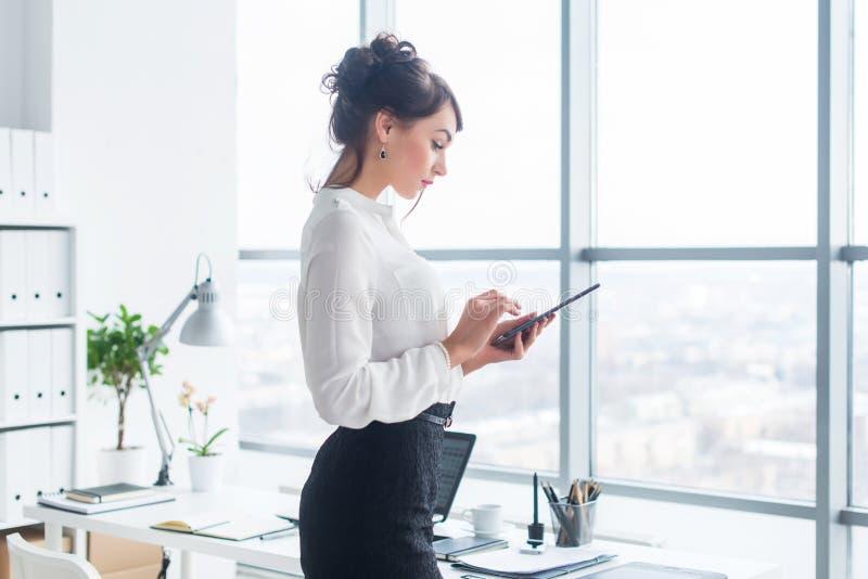 Zakończenie bocznego widoku portret pracownik texting, wysyła i czyta wiadomości podczas jej przerwy przy miejscem pracy, obraz royalty free