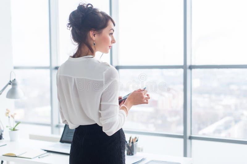 Zakończenie bocznego widoku portret pracownik texting, wysyła i czyta wiadomości podczas jej przerwy przy miejscem pracy, obrazy royalty free