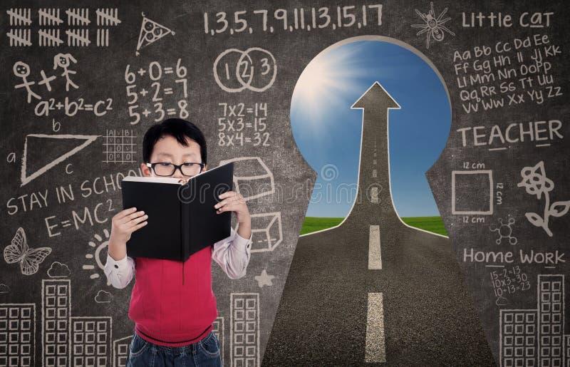 Zakończenie chłopiec czytelnicza książka z chalkboard i sukces drogą zdjęcie stock