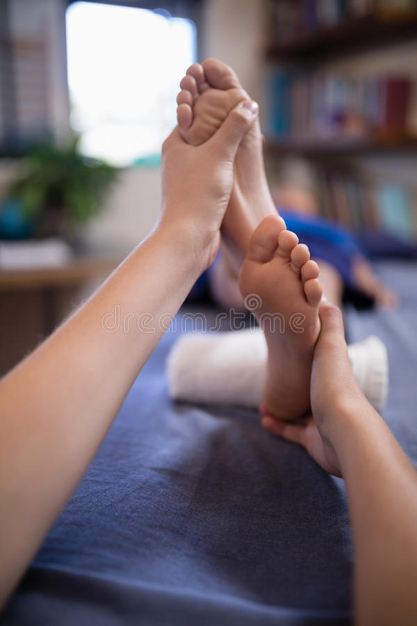 Zakończenie chłopiec odbiorczy nożny masaż od młodego żeńskiego terapeuta obrazy stock