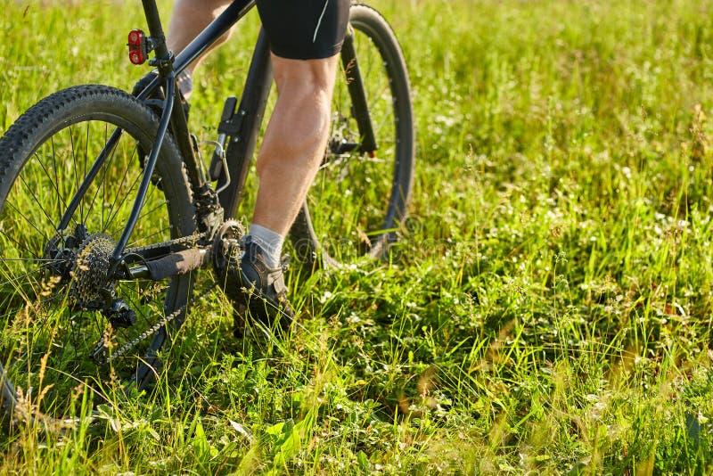 Zakończenie cyklisty mężczyzna iść na piechotę jeździeckiego rower górskiego na zielonej łące zdjęcie stock
